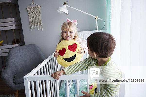 Porträt eines lächelnden kleinen Mädchens in der Krippe mit ihrem Bruder im Vordergrund