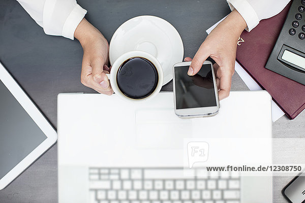 Woman with cup of coffee using smartphone  laptop