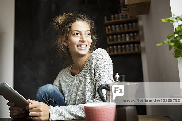 Smiling woman sitting at table holding tablet