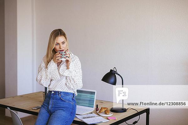 Junge Frau  die im Büro arbeitet  eine Pause macht  Kaffee trinkt