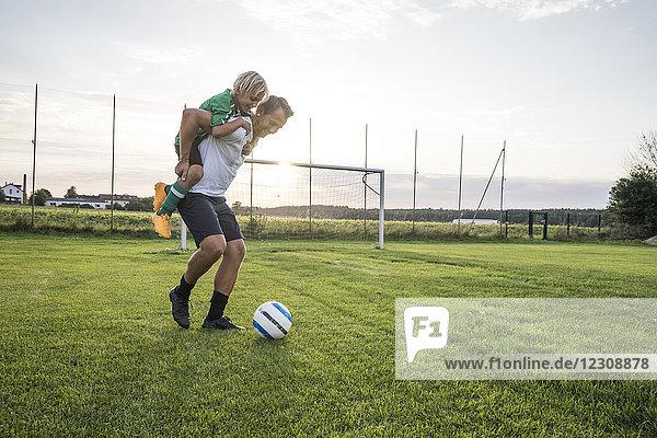 Trainer mit jungem Fußballspieler bei Sonnenuntergang auf dem Fußballplatz