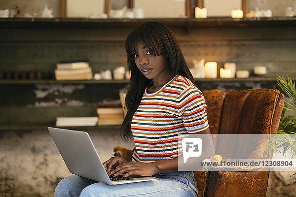 Porträt einer jungen Frau  die auf einem alten Ledersessel sitzt und auf einem Laptop in einem Loft arbeitet.