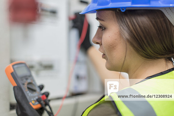 Young female electrician working with voltmeter at fusebox