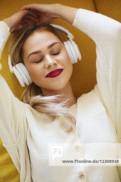 Blonde Frau mit Kopfhörer auf Sofa liegend