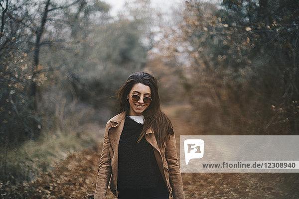 Porträt einer lächelnden jungen Frau in herbstlicher Natur