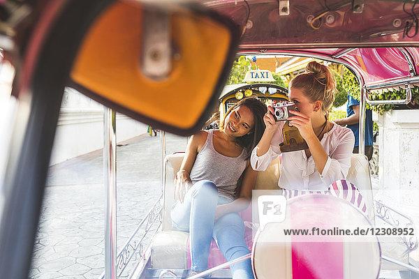 Thailand  Bangkok  zwei Freunde auf Tuk Tuk Tuk beim Fotografieren mit einer alten Kamera