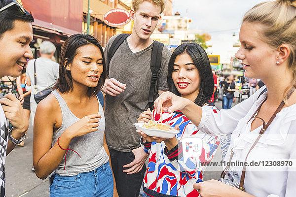 Thailand  Bangkok  Khao San Road  Gruppe von Freunden  die auf dem Straßenmarkt lokale Speisen kosten