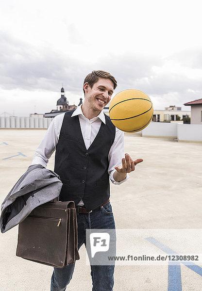 Glücklicher Geschäftsmann mit Basketball im Parkhaus