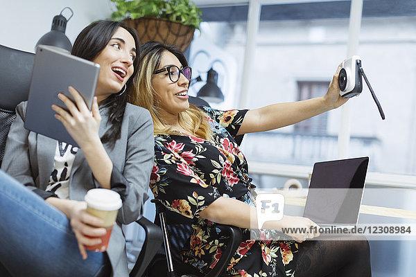 Zwei glückliche junge Frauen im Büro  die einen Selfie nehmen.
