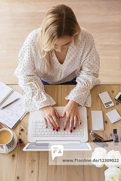 Junge Frau am Schreibtisch sitzend  mit Laptop