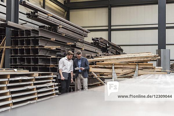 Zwei Männer mit Tablette in der Fabrik