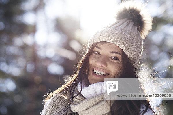 Porträt einer glücklichen jungen Frau im Winterwald