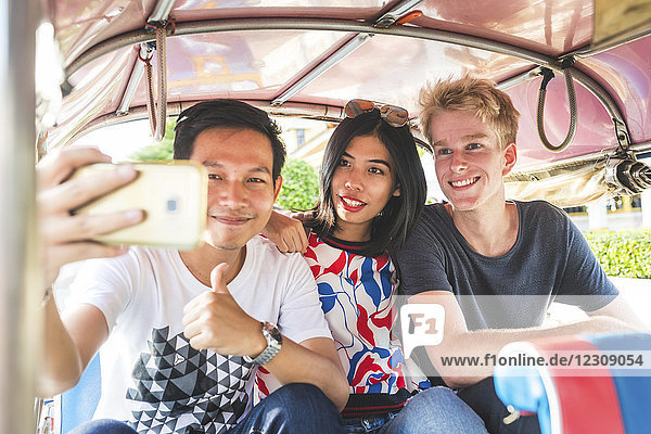 Thailand,  Bangkok,  drei Freunde auf Tuk Tuk Tuk,  die Selfie mit Smartphone fahren