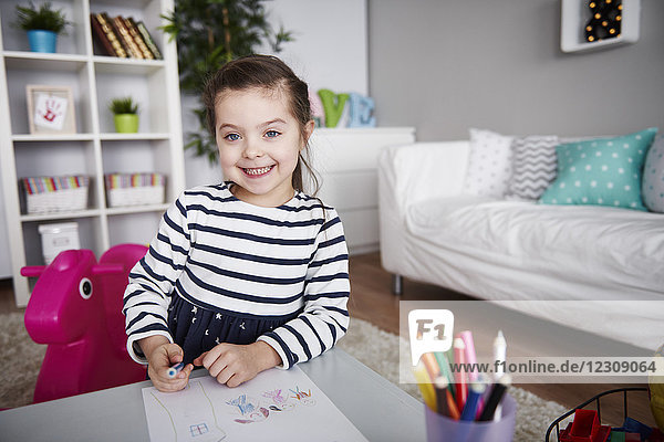 Portrait of little girl drawing in the living room