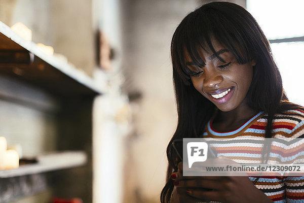 Porträt einer lächelnden jungen Frau mit dem Handy