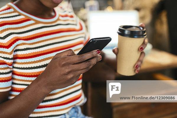 Frau hält Kaffee zum Mitnehmen während der Benutzung des Smartphones  Nahaufnahme