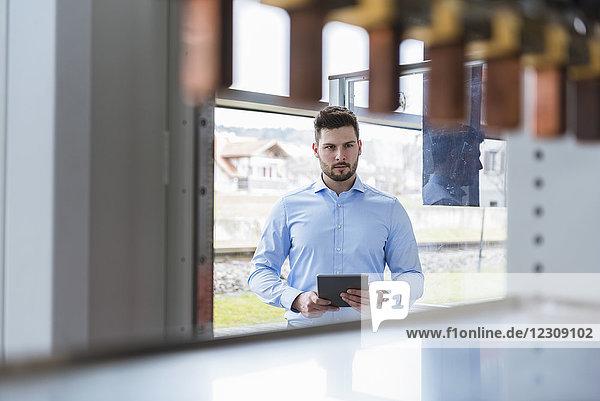 Geschäftsmann mit Tablette in der Firma beim Betrachten des Produktes