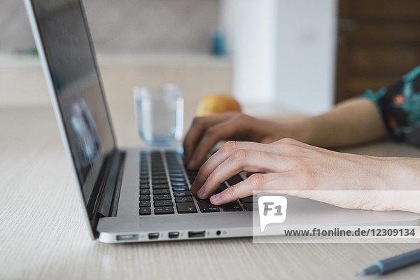 Nahaufnahme der Frau zu Hause mit Laptop auf dem Tisch