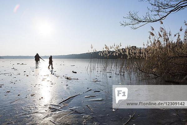 Deutschland  Brandenburg  Straussee  zugefrorener See und Silhouetten von zwei Menschen  die auf dem Eis laufen.