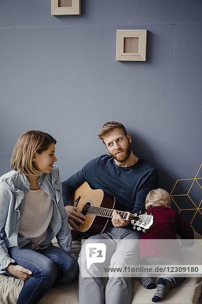 Glückliche Familie  die mit ihrem Sohn zu Hause Musik spielt.
