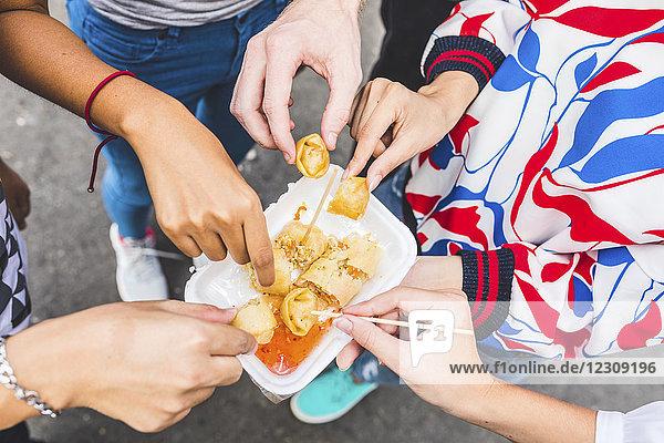 Thailand,  Bangkok,  Khao San Road,  Gruppe von Freunden,  die lokale Speisen auf dem Straßenmarkt probieren,  Nahaufnahme