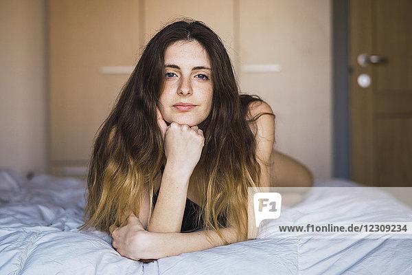 Porträt einer jungen Frau auf dem Bett liegend