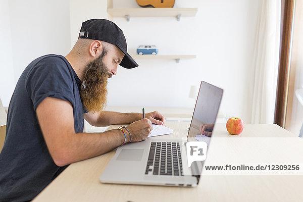 Ein bärtiger junger Mann sitzt am Schreibtisch mit einem Laptop  der etwas aufschreibt.