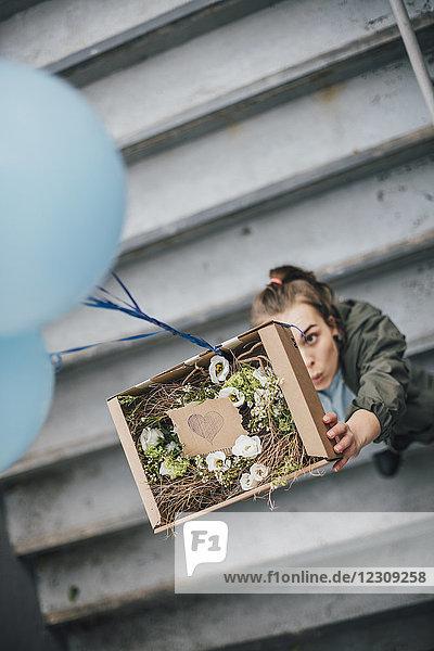 Frau schickt Geschenk im Karton mit Luftballons
