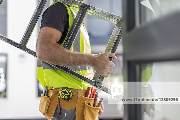 Close-up of construction worker carrying ladder