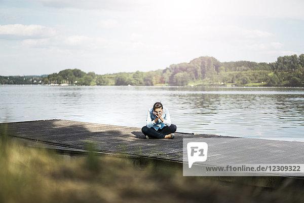 Entspannte Frau sitzt auf einem Steg am See