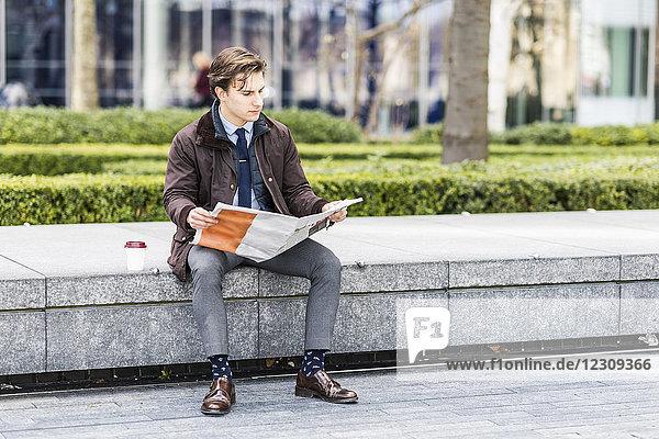 Geschäftsmann beim Zeitungslesen im Freien