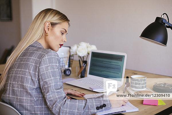 Junge Geschäftsfrau im Büro mit Laptop