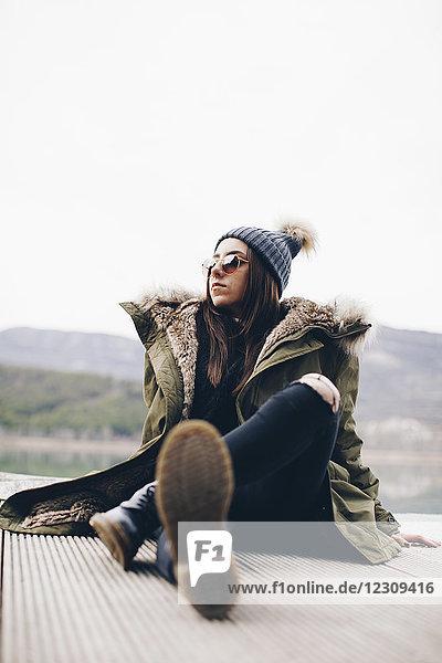 Porträt einer jungen Frau mit Sonnenbrille und Pudelmütze am Steg