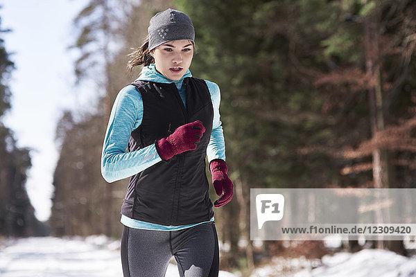 Junge Frau beim Joggen im Winterwald
