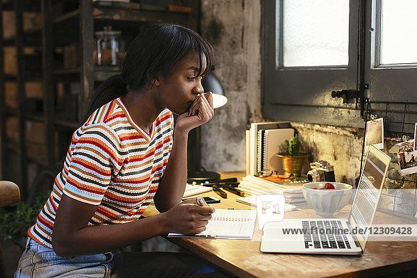 Nachdenkliche junge Frau sitzt am Schreibtisch in einem Loft und schaut auf den Laptop.