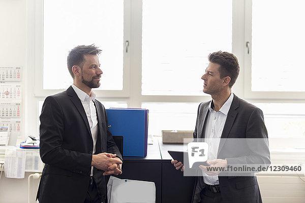 Zwei Geschäftsleute im Amt  die Lösungen diskutieren  mit dem digitalen Tablett
