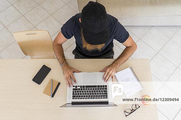 Junger Mann mit Baseballmütze am Schreibtisch mit Laptop  Draufsicht