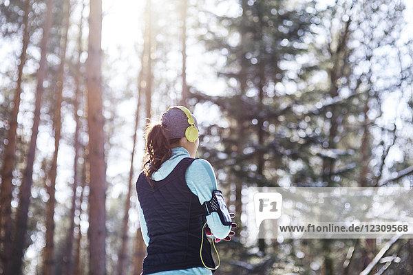 Rückansicht des jungen Joggers mit Kopfhörer im Wald bei einer Pause