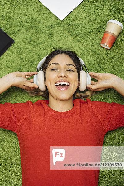 Fröhliche junge Frau liegt auf dem Teppich und hört Musik mit Kopfhörern.