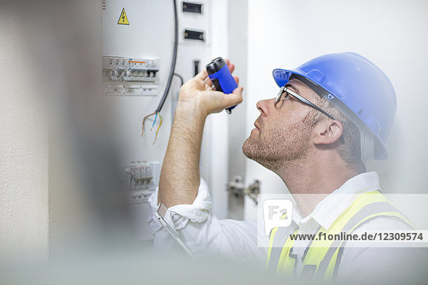 Electrician with flashlight at fusebox