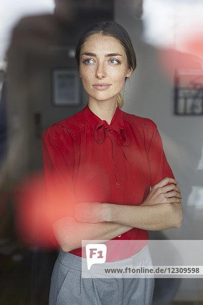 Porträt einer Frau in roter Bluse  die hinter einer Fensterscheibe steht.