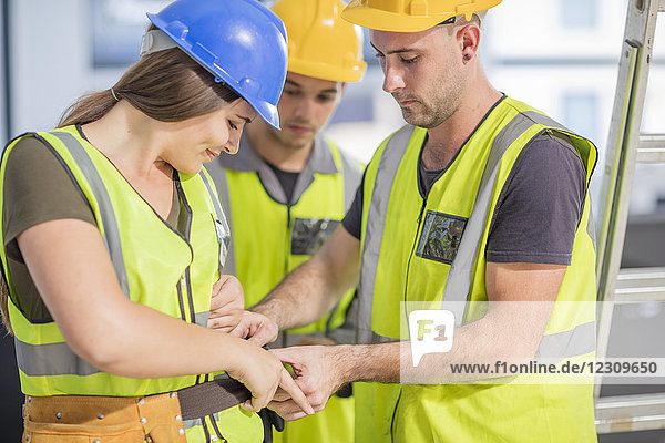 Construction worker helping colleague with tool belt