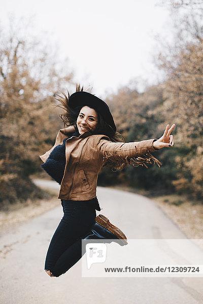 Porträt einer glücklichen jungen Frau  die in die Luft springt.