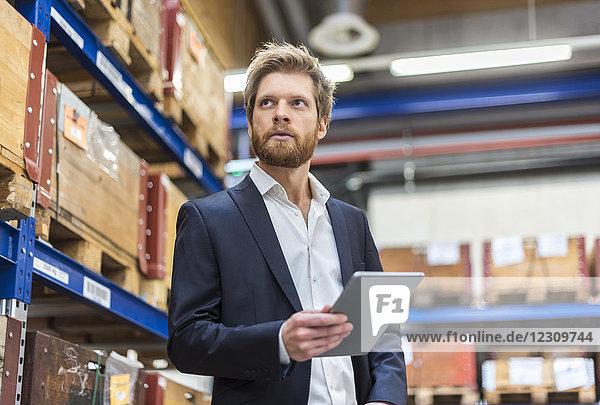 Geschäftsmann mit Tablette im Fabriklager und Blick in die Umgebung