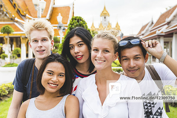 Thailand,  Bangkok,  Gruppenbild von fünf Freunden beim Besuch des Tempelkomplexes