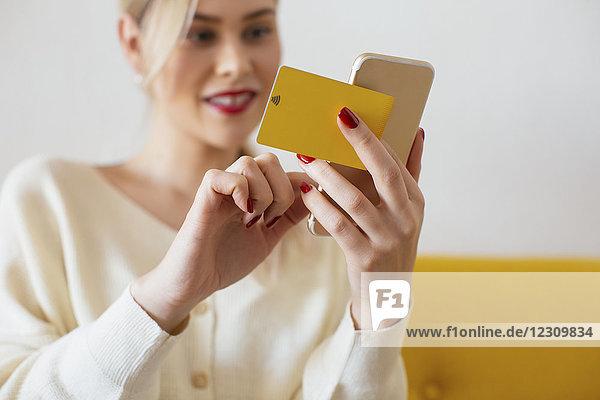 Frau mit Smartphone und Bankkarte zu Hause