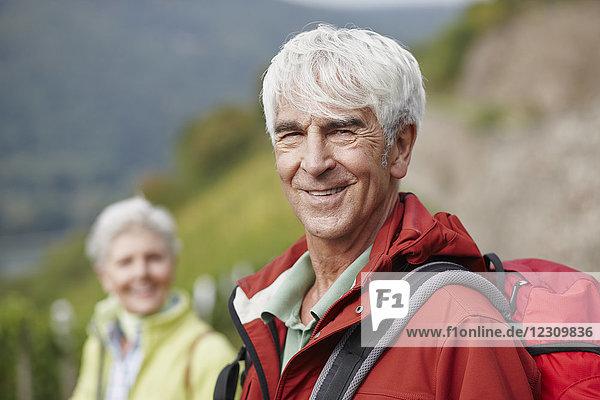 Porträt eines lächelnden Senioren mit Rucksack