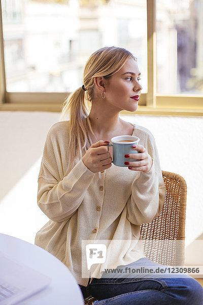 Blonde Frau mit einer Tasse Kaffee  die aus dem Fenster schaut.