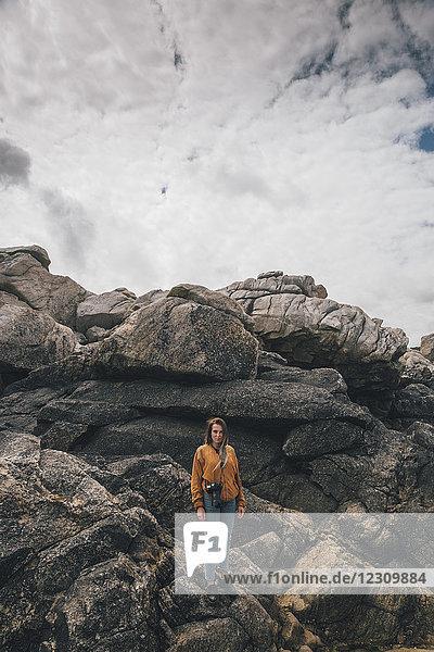 Frankreich,  Bretagne,  Plouguerneau,  Saint-Michel,  junge Frau mit Kamera in Felsen an der Küste stehend