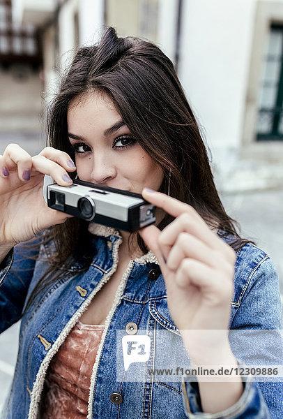 Porträt einer brünetten Frau mit einer alten Kamera in einer Stadt